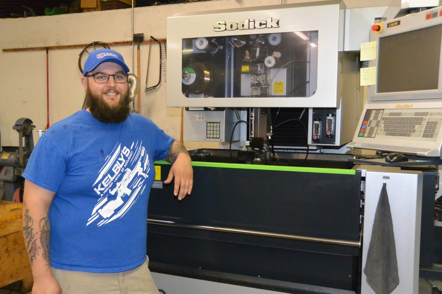 "Ian Kelbly with the wire EDM machine used to ""cut"" the bolt races"
