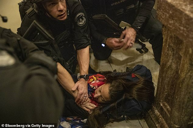 38436222-9183085-Officers_were_later_seen_tending_to_the_bleeding_woman_on_the_fl-a-10_1611570...jpg